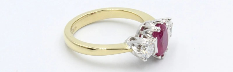 yellow gold ruby and diamond engagement ring on a white background
