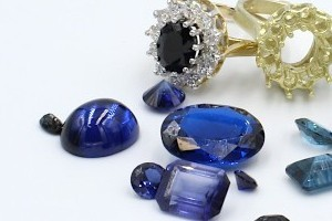 loose blue sapphires next to a gold engagement ring