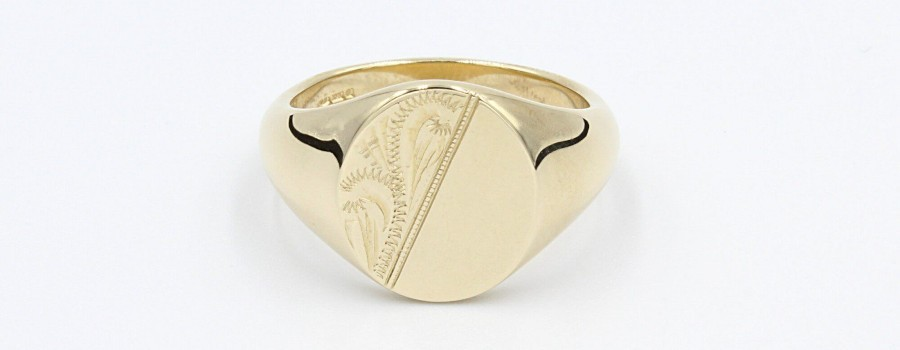 a gold signet ring with a half engraved surface on a white background