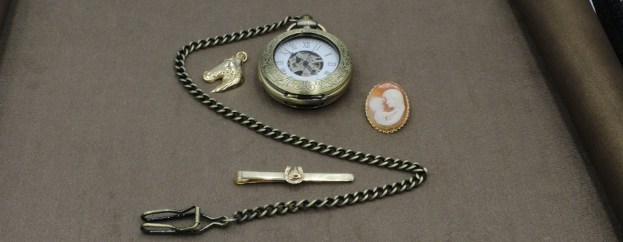 an old pocket watch and other items of jewellery on a brown cloth
