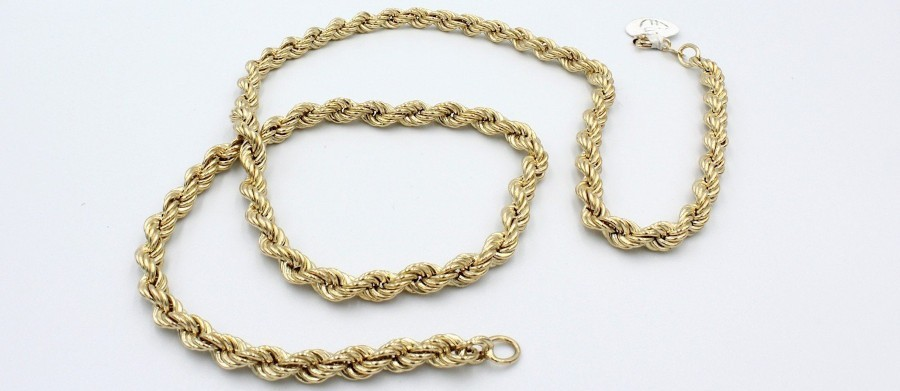 a thick gold rope necklace on a white background