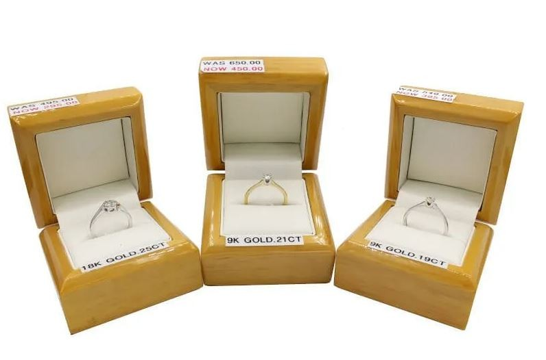 Three discounted engagement rings in their boxes on a white background