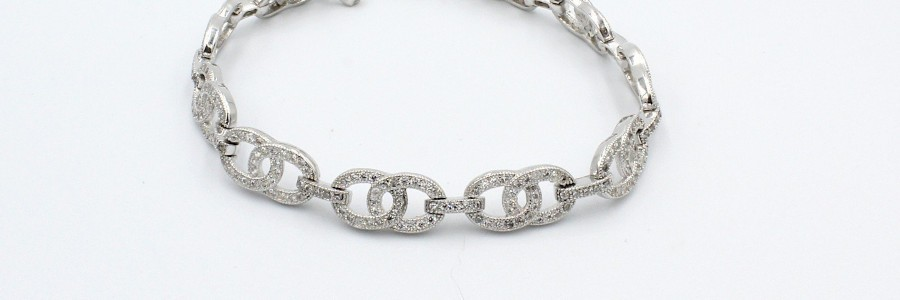 a silver fancy link bracelet on a white background
