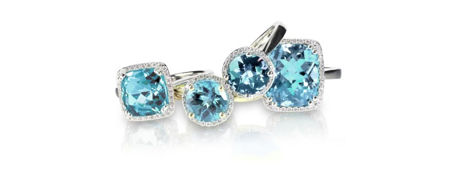 several blue zircon and white gold rings on a white background