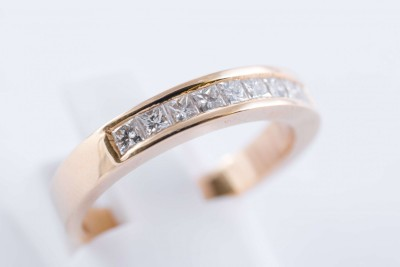 a gold and diamond half-eternity wedding ring on a white background