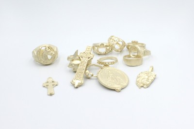 bits and pieces of raw gold jewellery on a white background