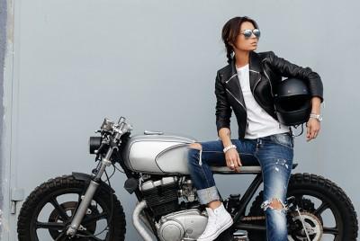 a stylish woman wearing a leather jacket sitting on a motorbike