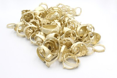 a pile of unpolished yellow gold rings on a white background