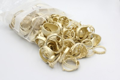 a bag of unpolished golden jewellery on a white background
