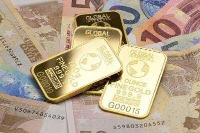 gold bullion laying on top of euro bank notes