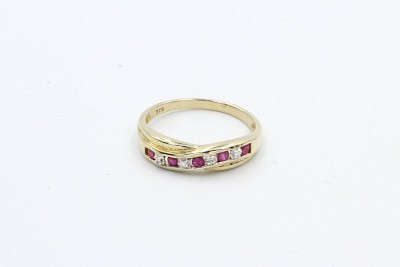 a half eternity gold twist ring with diamond and rubies on a white background