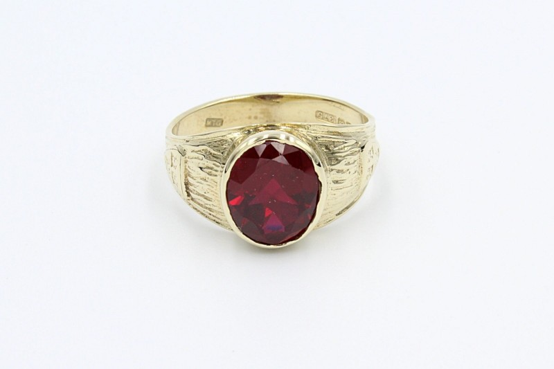 a gold college ring set with one large garnet gemstone on a white background