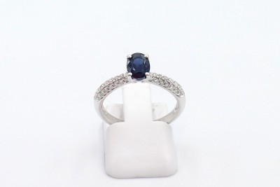 a solitaire blue sapphire ring, withd iamond set shoulders, on a white background