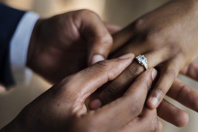 a man putting a diamond wedding ring on his fiances finger