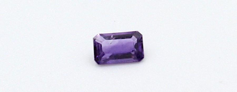 a single cut amethyst gemstone on a white background