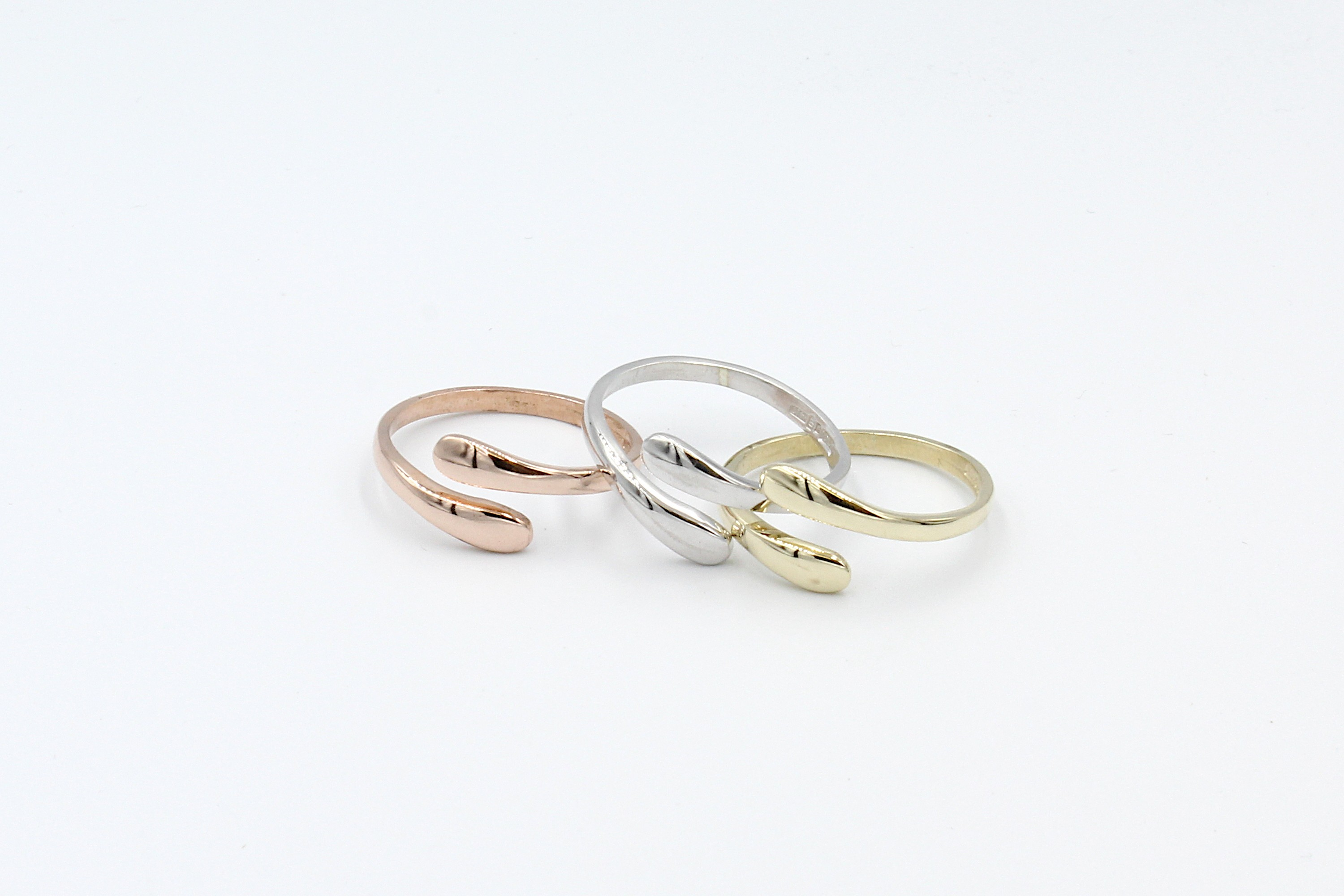 white gold, rose gold, and yellow goldthumb rings on a white background