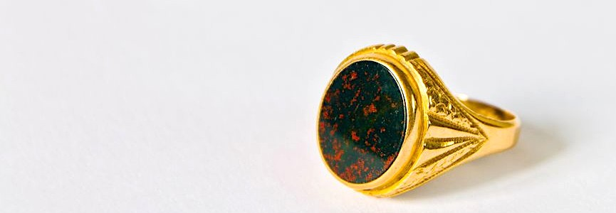 a gold college ring with a large bloodstone gem