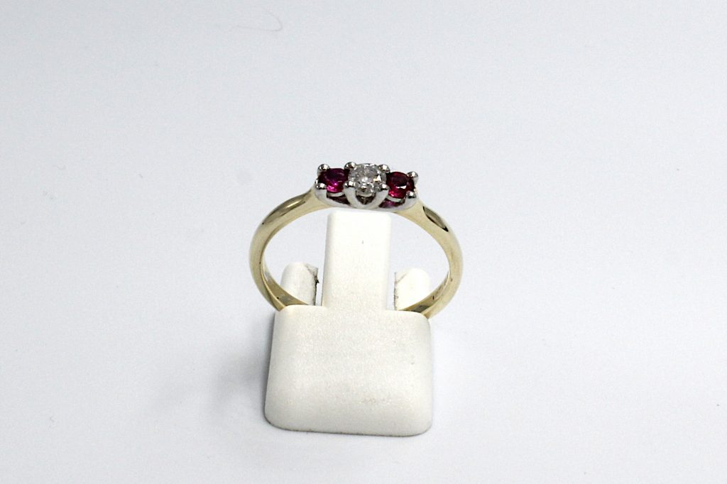 Front view of a diamond and ruby engagement ring made from gold