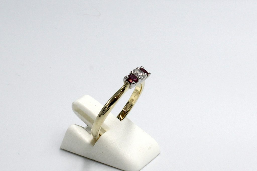 side view of a diamond and ruby engagement ring made from gold