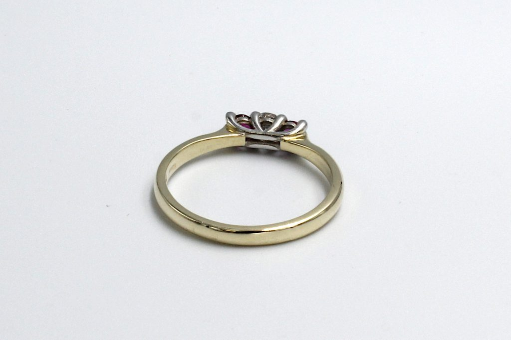 rear view of a diamond and ruby engagement ring made from gold