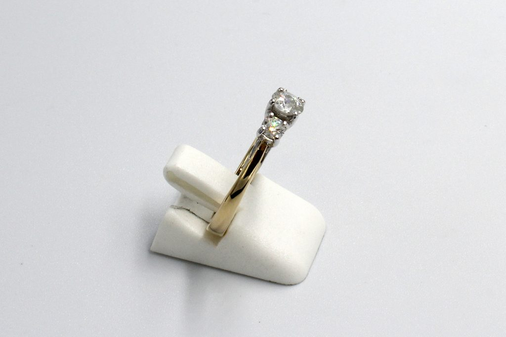 side view of a multi-diamond and gold engagement ring