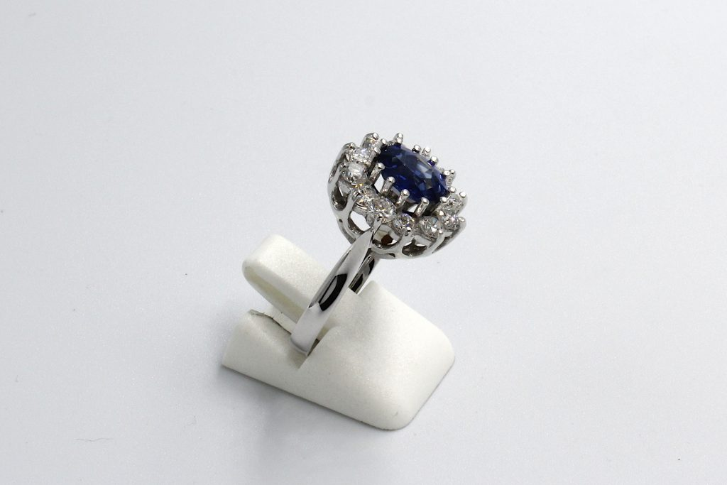 side view of a white gold diamond and sapphire cluster engagement ring