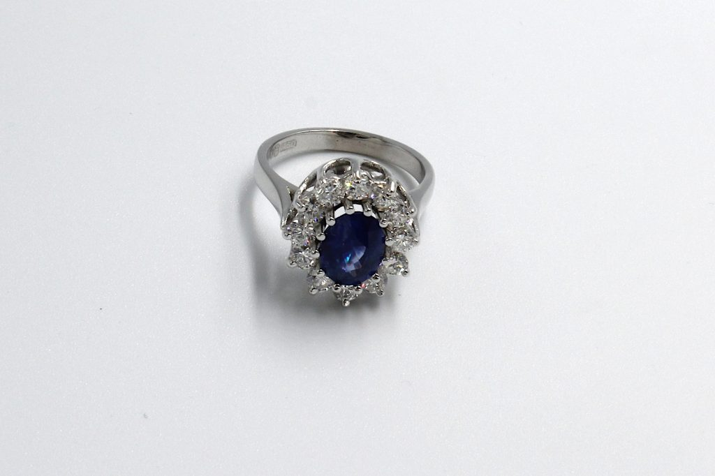 top view of a white gold diamond and sapphire cluster engagement ring