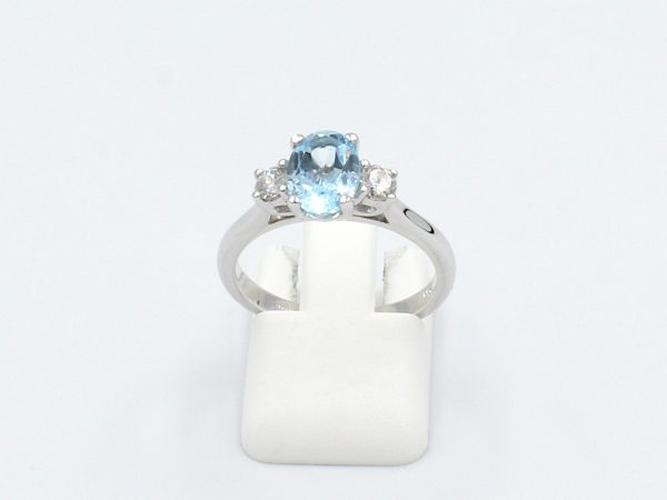 front view of aquamarine and diamond engagement ring on a white background
