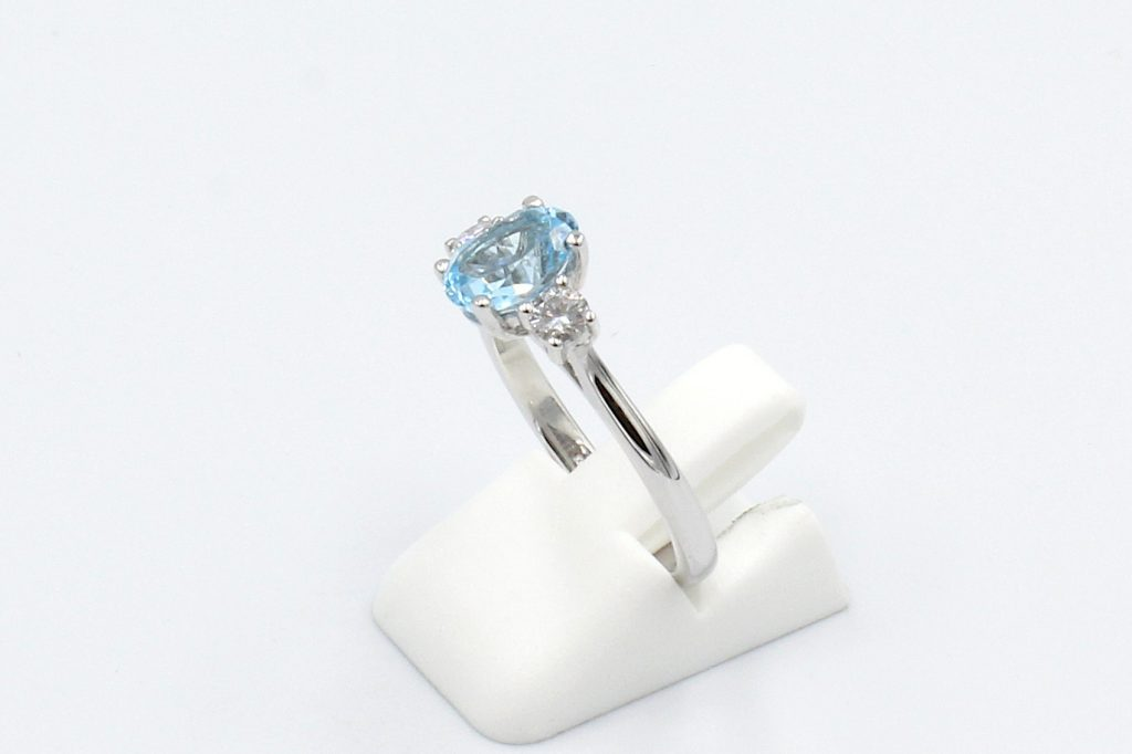 side view of aquamarine and diamond engagement ring on a white background
