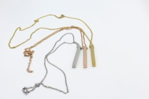 three bar necklaces on a white background