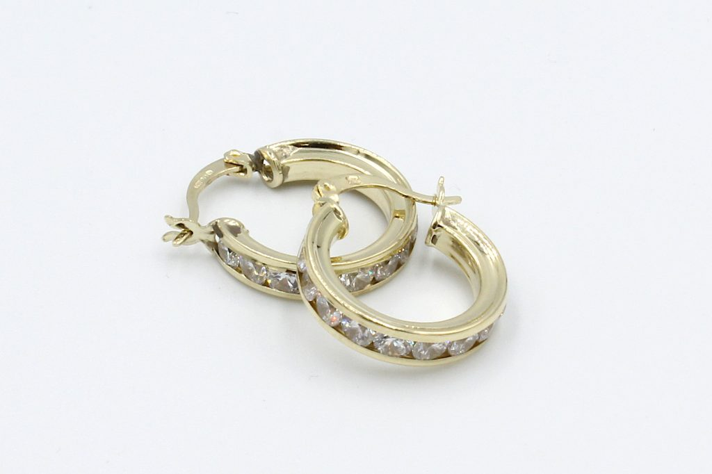 two gold cz hoop earrings laying on a white backgrounf