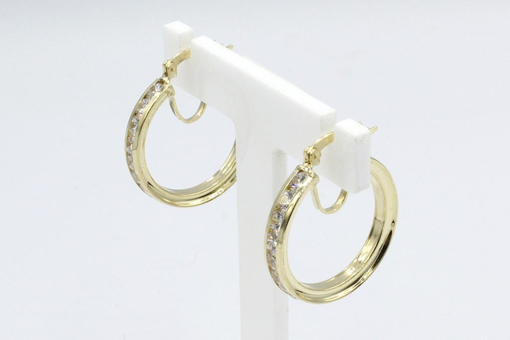side view of gold cz hoop earrings on white stand