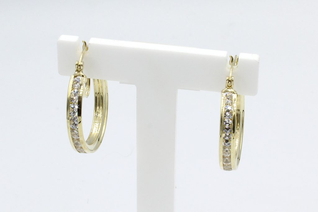 front view of gold cz hoop earrings on white stand