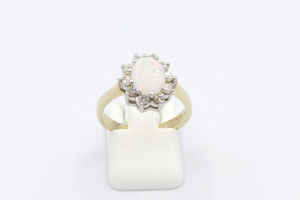 front view opal and diamond cluster ring on a white background