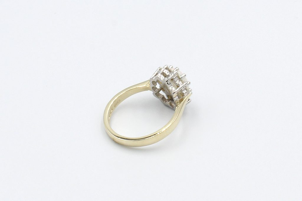 rear view opal and diamond cluster ring on a white background
