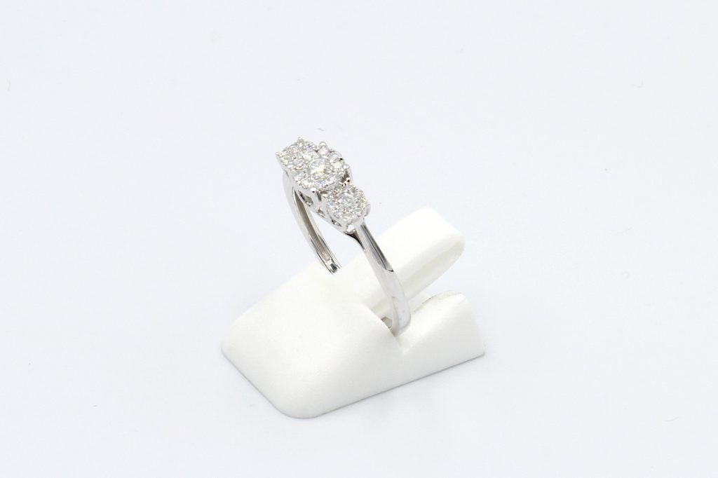 side view of white gold multi-diamond engagement ring on white background