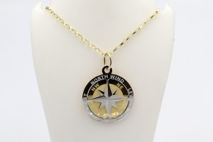 front view of a gold compass pendant on a gold chain