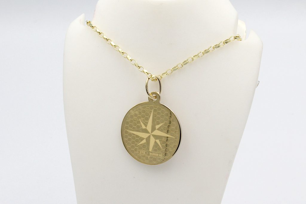 rear view of a gold compass pendant on a gold chain