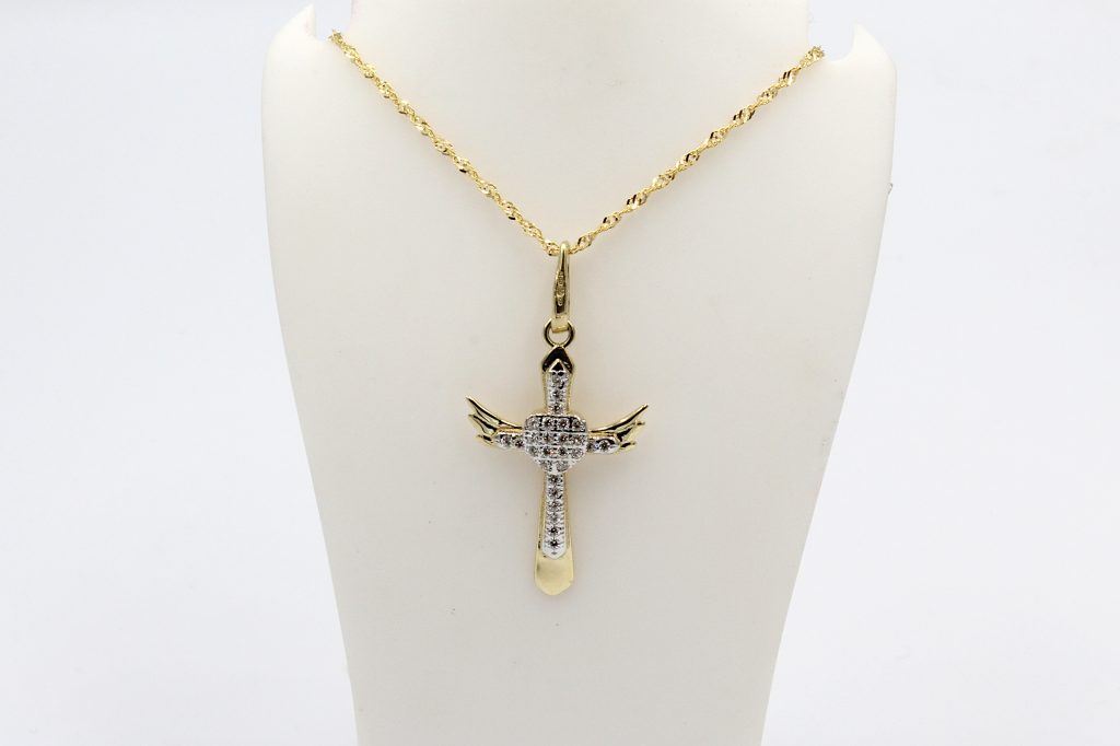 9k gold cross pendant on a prince of wales chain hanging from a white buust
