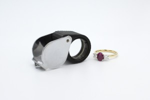 a jewellery looking glass laying next to a ruby engagement ring