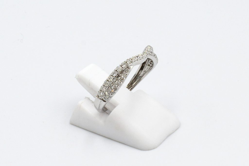 side view of a shaped and twisted wedding ring encrusted with diamonds