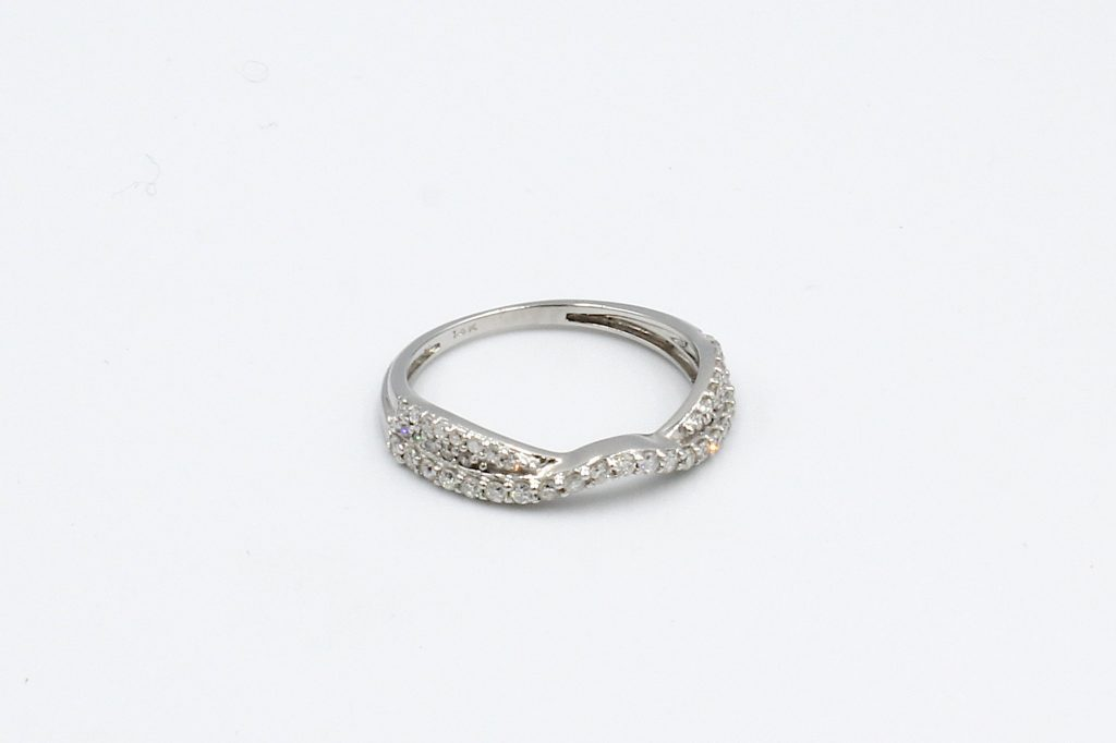top view of a shaped and twisted wedding ring encrusted with diamonds