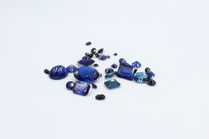 several blue loose sapphire gems on a white backgroun