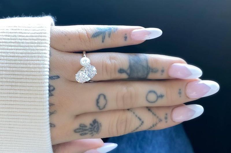 ariana grande's pearl and diamond ring on her tattooed hand