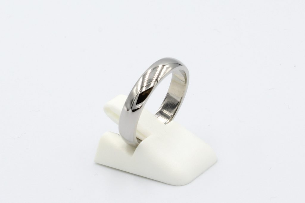 side view of a platinum wedding ring on a white background