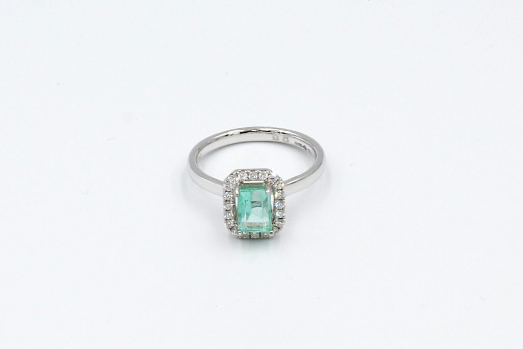 top view of an emerald and diamond halo engagement ring made from platinum.