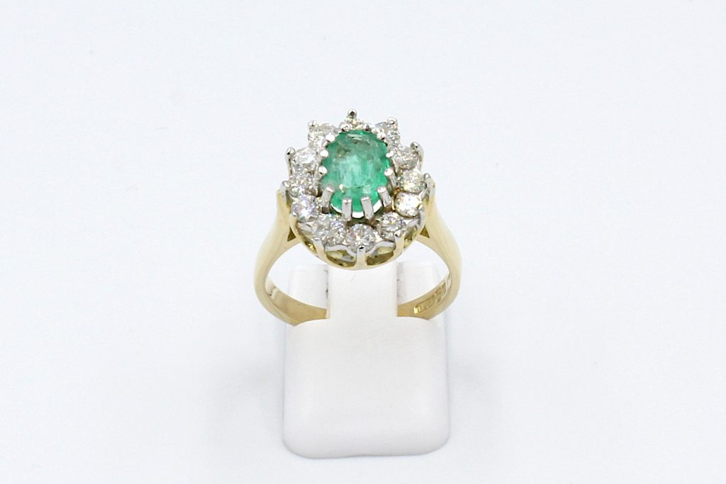 front view of an emerald and diamond cluster ring made from gold.