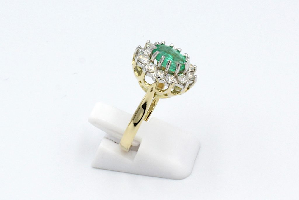 side view of an emerald and diamond cluster ring made from gold.