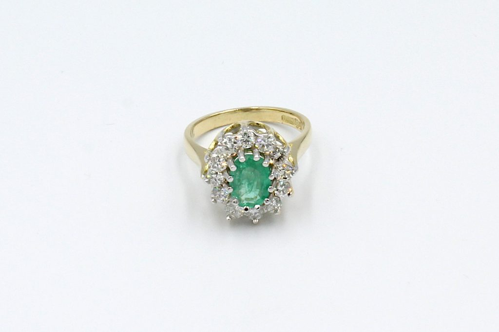 top view of an emerald and diamond cluster ring made from gold.