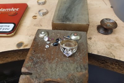 a diamond engagement ring and jewels laying on a jewellery workbench